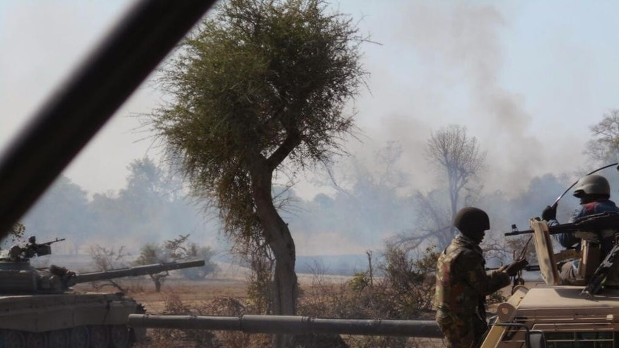 In this photo made available by the Nigerian Military taken Tuesday, April 28, 2015, Nigerian military personnel in action during an attack on Islamic extremists in the Sambisa Forest, Nigeria. Nigeria's military rescued 234 more girls and women from a Boko Haram forest stronghold in the country's northeast, an announcement on social media said Saturday, May 2, 2015. (Nigerian Military via AP)