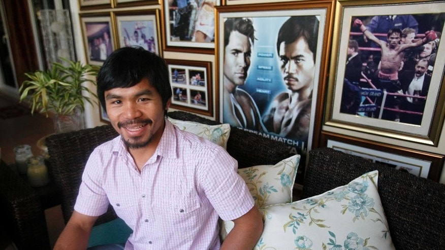 FILE - In this April 20, 2010 file photo, Filipino boxer Manny Pacquiao smiles during an unscheduled news conference at his mansion in General Santos city in southern Philippines. Pacquiao has been an inspiration for millions of Filipinos not just as a boxer, but as a philanthropist. As a politician, not so much. The country's biggest individual taxpayer in 2013, Pacquiao has often shared his wealth with the poor in his home province of Sarangani, where he has been elected and re-elected to Congress on waves of adoration. Win or lose in his May 2 megafight with Floyd Mayweather, Pacquiao is a lock to keep his seat for a third and final term, unless he decides to run for another office such as senator. (AP Photo/Bullit Marquez, File)