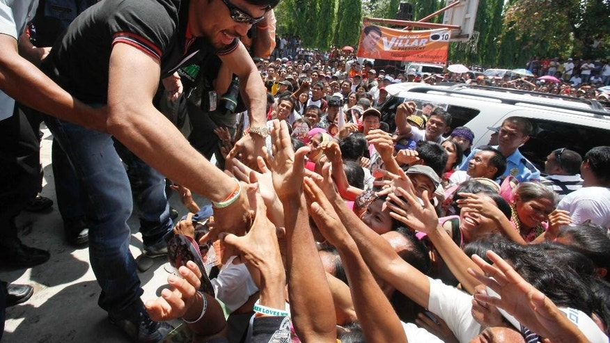 FILE - In this March 26, 2010 file photo, Filipino boxer Manny Pacquiao greets supporters upon arrival at Maasim, Sarangani province for a political rally in southern Philippines. Pacquiao has been an inspiration for millions of Filipinos not just as a boxer, but as a philanthropist. As a politician, not so much. The country's biggest individual taxpayer in 2013, Pacquiao has often shared his wealth with the poor in his home province of Sarangani, where he has been elected and re-elected to Congress on waves of adoration. Win or lose in his May 2 megafight with Floyd Mayweather, Pacquiao is a lock to keep his seat for a third and final term, unless he decides to run for another office such as senator. (AP Photo/Bullit Marquez, File)