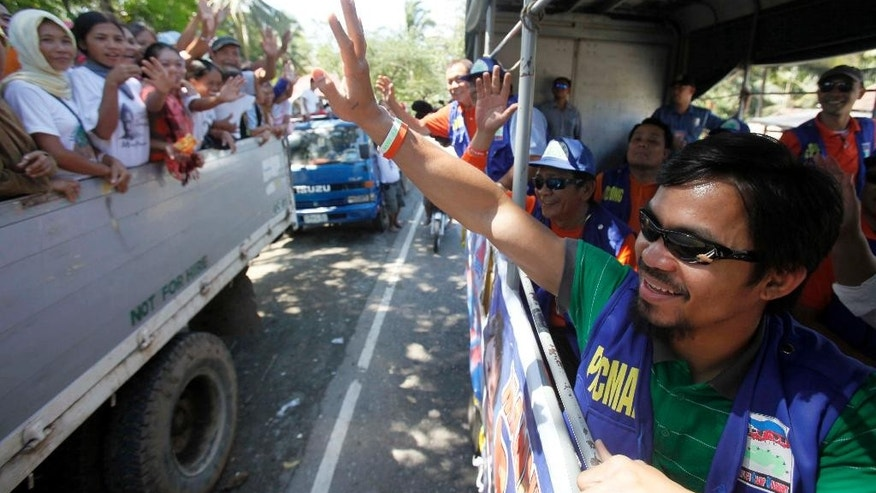 FILE - In this March 27, 2010, Filipino boxer Manny Pacquiao, then candidate for Congressman at the seven-township Sarangani province, greets supporters as his campaign motorcade makes the rounds of townships on the second day of the official campaign period in Malungon township, Sarangani province in southern Philippines. Pacquiao has been an inspiration for millions of Filipinos not just as a boxer, but as a philanthropist. As a politician, not so much. The country's biggest individual taxpayer in 2013, Pacquiao has often shared his wealth with the poor in his home province of Sarangani, where he has been elected and re-elected to Congress on waves of adoration. Win or lose in his May 2 megafight with Floyd Mayweather, Pacquiao is a lock to keep his seat for a third and final term, unless he decides to run for another office such as senator. (AP Photo/Bullit Marquez, File)