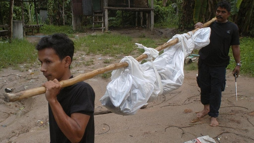 Thai rescuers carry a dead body to a hospital in Songkhla province, southern of Thailand Friday, May 1, 2015. Police in Thailand found dozens of shallow graves Friday and at least one corpse in an isolated mountain shelter that is believed to be a trafficking camp for ethnic Rohingya Muslims fleeing Myanmar. (AP Photo/Sumeth Panpetch)