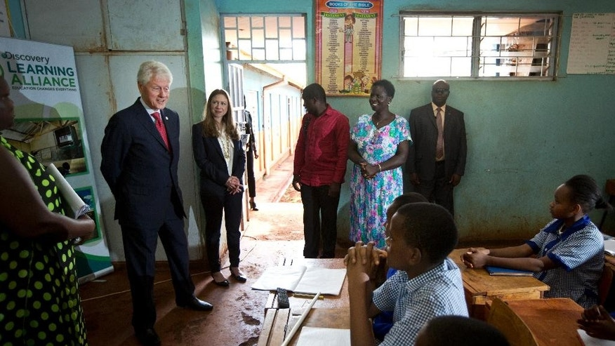 Former President Bill Clinton, left, and daughter Chelsea Clinton, center-left, visit a classroom to hear a lesson for pupils, scheduled for their visit, about the functioning of the female reproductive system, in the Farasi Lane Primary School in Nairobi, Kenya Friday, May 1, 2015. Former President Bill Clinton and daughter Chelsea Clinton are in the East African nation of Kenya as part of a wider tour of projects run by the family's Clinton Foundation. (AP Photo/Ben Curtis)