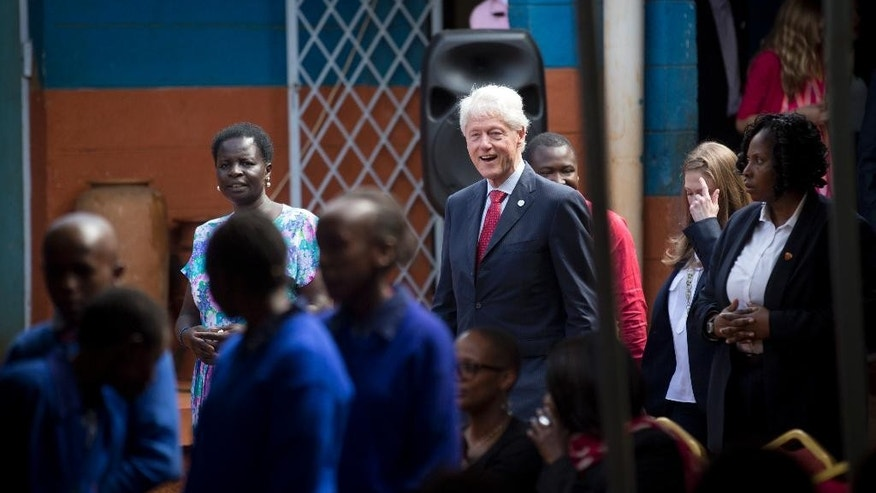 """Former President Bill Clinton, center, and daughter Chelsea Clinton, 2nd right, arrive to speak about their foundation's """"No Ceilings"""" project about the participation of women and girls globally, at the Farasi Lane Primary School in Nairobi, Kenya Friday, May 1, 2015. Former President Bill Clinton and daughter Chelsea Clinton are in the East African nation of Kenya as part of a wider tour of projects run by the family's Clinton Foundation. (AP Photo/Ben Curtis)"""