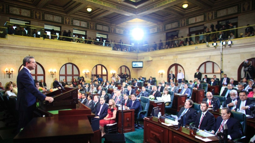 Puerto Rico Gov. Alejandro Garcia Padilla, left, delivers his budget address for the next fiscal year at the Capitol building in San Juan, Thursday, April 30, 2015. Legislators struck down a key part of a plan to overhaul the island's tax system early Thursday, raising concerns about the U.S. territory's economic future and its ability to pay off a heavy public debt.  (AP Photo/Ricardo Arduengo)