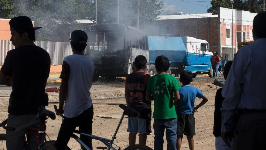 People watch as a torched passenger bus smolders after it was extinguished by firefighters in Guadalajara, Mexico, Friday, May 1, 2015. Authorities in western Mexico are asking residents to stay at home as they scramble to extinguish burning vehicles blocking roads in various parts of Guadalajara. Such blockades are a common cartel response to the arrest of important members or are used to foil police and military operations. (AP Photo/Refugio Ruiz)