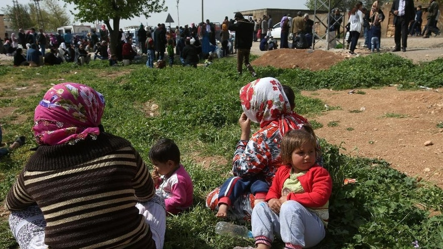 In this picture taken on Monday, April 20, 2015, Kurdish refugees who fled from Kobani wait for the opening of a border gate to return to their town, at the Mursitpinar border crossing in Suruc town, Turkey. Three months since Kobani was liberated, tens of thousands of its residents are still stranded in Turkey, reluctant to return to a wasteland of collapsed buildings and at a loss as to how and where to rebuild their lives. (AP Photo/Hussein Malla)