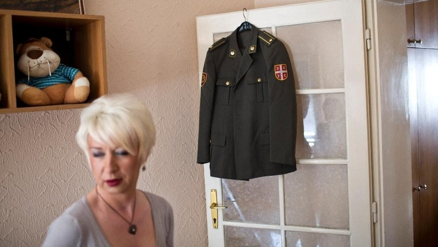 Helena, a transgender person, stands next to her Serbian army uniform put on display in her friend's apartment Wednesday, April 15, 2015, in Belgrade, Serbia. Maj. Helena knew that revealing herself as Serbia's first transgender officer would mean the end of her military career. In the bastion of the Serbian macho world, there was simply no room for a soldier who was going to become a woman. So, after more than twenty years of service, Helena agreed to leave. But, she didn't go quietly. (AP Photo/Marko Drobnjakovic)