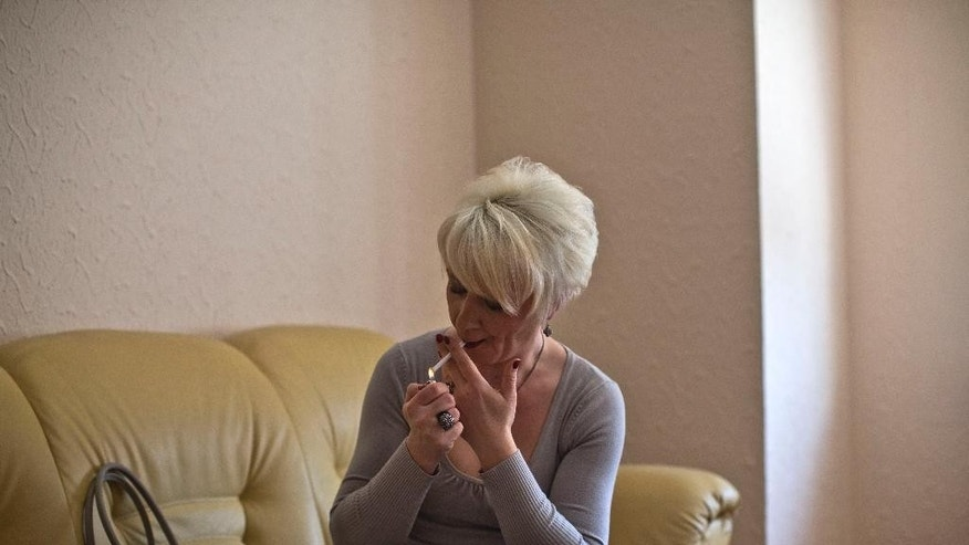 Helena, a transgender person, lights a cigarette in her friend's apartment in Belgrade, Serbia Wednesday, April 15, 2015. Maj. Helena knew that revealing herself as Serbia's first transgender officer would mean the end of her military career. In the bastion of the Serbian macho world, there was simply no room for a soldier who was going to become a woman. So, after more than twenty years of service, Helena agreed to leave. But, she didn't go quietly. (AP Photo/Marko Drobnjakovic)