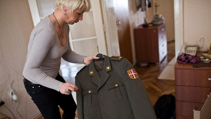 Helena, a transgender person, holds her Serbian army uniform Wednesday, April 15, 2015, at her friend's apartment in Belgrade, Serbia. Maj. Helena knew that revealing herself as Serbia's first transgender officer would mean the end of her military career. In the bastion of the Serbian macho world, there was simply no room for a soldier who was going to become a woman. So, after more than twenty years of service, Helena agreed to leave. But, she didn't go quietly. (AP Photo/Marko Drobnjakovic)