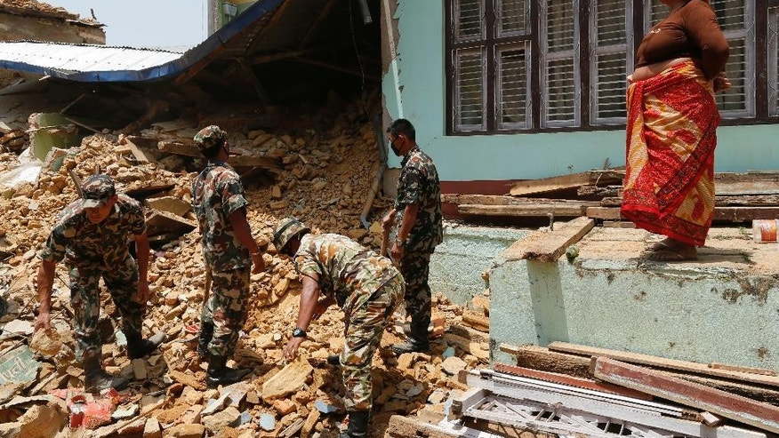 A local woman watches Nepalese soldiers dig through the rubble of a collapsed home in search of bodies in the Manakamana village, near the epicenter of last week's massive earthquake, in the Gorkha District of Nepal, Friday, May 1, 2015. (AP Photo/Wally Santana)