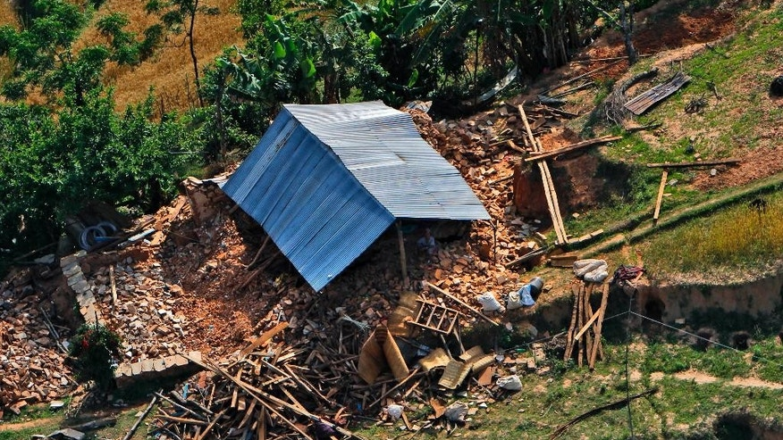 A man sits under the tin roof of a house destroyed in an earthquake, as seen from an Indian Air Force helicopter in Melamchi, Sindhupalchowk district, Nepal, Friday, May 1, 2015. The U.N. said the quake affected 8.1 million people, more than a fourth of Nepal's population of 27.8 million, and that more than 1.4 million needed food assistance. (AP Photo/Niranjan Shrestha)