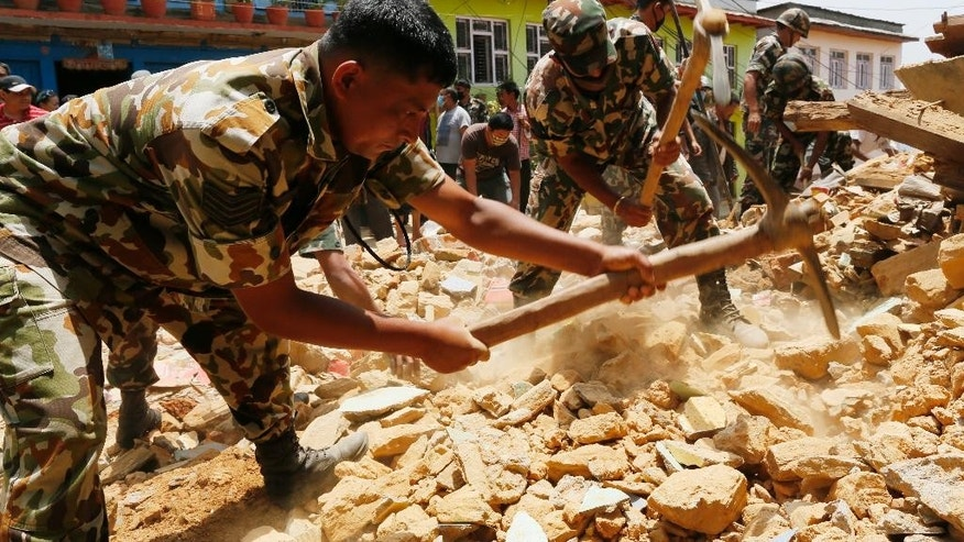 Nepalese soldiers dig for a rumored missing person in the rubble of a collapsed house in the Manakamana village known for its spiritual Hindu temple, near the epicenter of last week's massive earthquake, in the Gorkha District of Nepal, Friday, May 1, 2015. (AP Photo/Wally Santana)