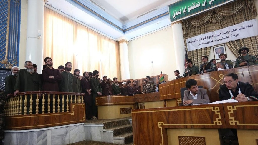 Defendants attend their trial at the Primary Court in Kabul, Afghanistan, Saturday, May 2, 2015. The trial of 49 suspects, including 19 police officers, on charges relating to the mob killing of an Afghan woman began in the capital, Kabul, on Saturday. The opening of the trial at Afghanistan's Primary Court was broadcast live on nationwide television. The suspects all face charges relating to the March 19 killing of a 27-year-old woman named Farkhunda. (AP Photo/Rahmat Gul)