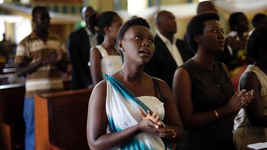 Friends and relatives of Jean Claude Niyonzima, who was killed during clashes with police over the move by President Pierre Nkurunziza to seek a third term in office, gather for his funeral service at the Regina Mundi cathedral in Bujumbura, Burundi, Saturday May 2, 2015. Many people have gathered in the streets over the past few days to protest against President Pierre Nkurunziza's decision to run for election as president for a third term in office. (AP Photo/Jerome Delay)