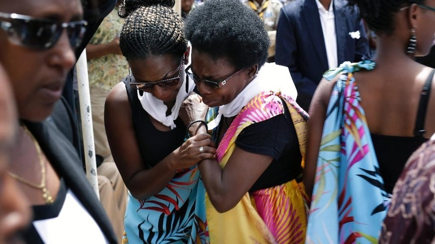 Friends and relatives of Jean Claude Niyonzima, who was killed during clashes with police over  the move by President Pierre Nkurunziza to seek a third term, weep during his burial ceremony outside Bujumbura, Burundi, Saturday May 2, 2015.  Many people have gathered in the streets over the past few days to protest against President Pierre Nkurunziza's decision to run for election as president for a third term in office. (AP Photo/Jerome Delay)