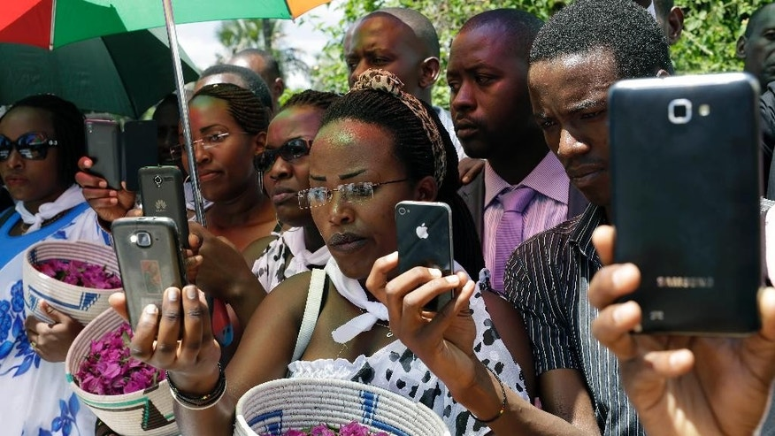 Friends and relatives of Jean Claude Niyonzima, who was killed during clashes with police over the move by President Pierre Nkurunziza to seek a third term in office, take pictures during his burial ceremony outside Bujumbura, Burundi, Saturday May 2, 2015.  Many people have gathered in the streets over the past few days to protest against President Pierre Nkurunziza's decision to run for election as president for a third term in office. (AP Photo/Jerome Delay)