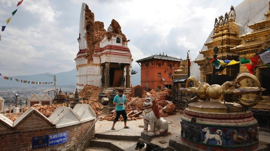 In this Thursday, April 30, 2015 photo, a man walks through the famous Swayambhunath stupa after it was damaged in the April 25 massive earthquake in Kathmandu, Nepal. Swayambhunath, which dates back to the 5th century, is one of at least 68 cultural heritage sites in Nepal that were damaged by the earthquake. (AP Photo/Niranjan Shrestha)