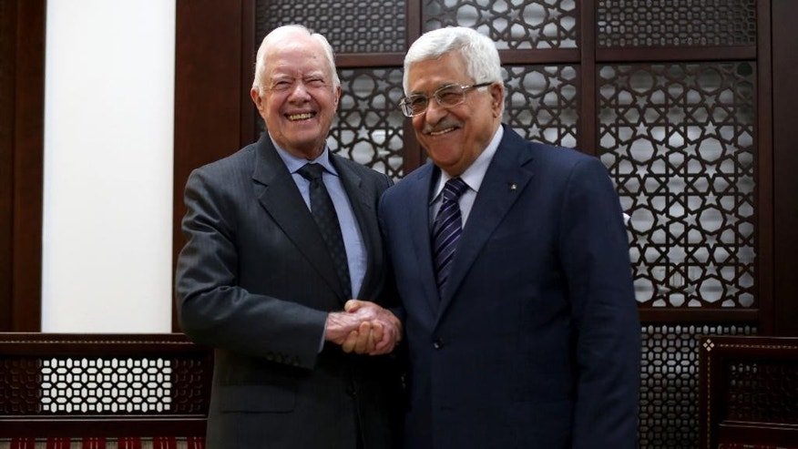 Palestinian President Mahmoud Abbas, right, shakes hands with Former U.S. President Jimmy Carter during their meeting on Saturday, May 2, 2015 in the West Bank city of Ramallah.  (Abbas Momani Pool Photo via AP)