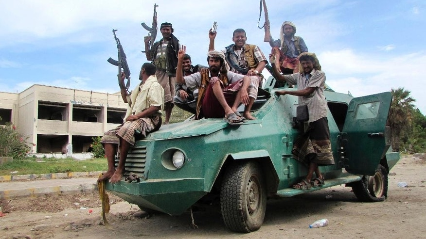 FILE - In this Friday, March 20, 2015 file photo, militiamen loyal to President Abed Rabbo Mansour Hadi ride on an army vehicle on a street in Aden, Yemen. Aden, once Yemen's commercial hub, has been hit by a month of unrelenting urban warfare as Shiite rebels and their allies in the military try to capture the city, battling with local militiamen as warplanes from a Saudi-led coalition pound the city with airstrikes trying to stop the rebel advance. (AP Photo/Yassir Hassan, File)