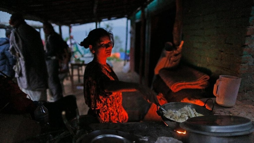 A woman believing that her faith in the Hindu gods saved her life in last week's massive earthquake, prepares dinner for her family in a makeshift kitchen after their house collapsed in Pujari village in the Gorkha District of Nepal, Friday, May 1, 2015. (AP Photo/Wally Santana)