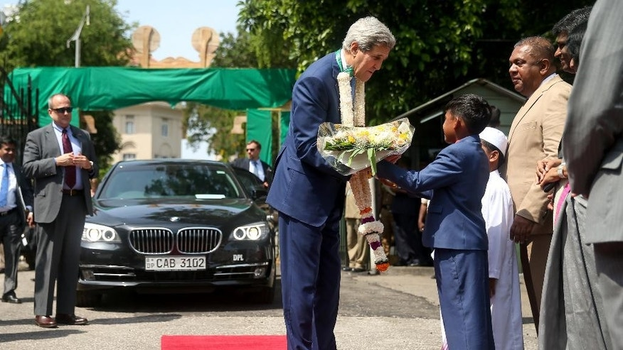 Children greet U.S. Secretary of State John Kerry, center,  as he arrives for a meeting with Sri Lankan Foreign Minister Mangala Samaraweera, right, at the Ministry of Foreign Affairs, Saturday, May 2, 2015, in Colombo, Sri Lanka. Kerry is visiting Sri Lanka, Kenya, and Djibouti on his trip. (AP Photo/Andrew Harnik, Pool)