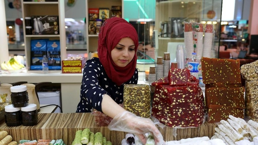 "In this Wednesday, April 29, 2015 photo, Rahaf Abdullah works at a sweets shop at a mall in Irbil, in Iraq's Kurdish region. Two years after fleeing from her home in Damascus, the 22-year-old is selling sweets to local women who largely refuse to take such jobs. ""The Kurdish girls are a bit conservative. No, a lot conservative,"" she says. (AP Photo/Bram Janssen)"