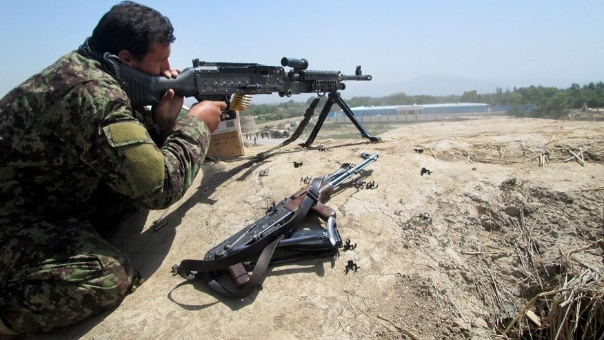 An Afghan security force aim his weapon during a battle with Taliban insurgents in the Chahardara district of Kunduz province northern of Kabul, Afghanistan, Sunday, May 3, 2015. Afghan officials say fierce fighting between government forces and Taliban insurgents in northern Afghanistan has forced thousands of people to flee their homes. Meher Khuda Sabar, an official in the Refugee and Repatriation Ministry, said Sunday around 2,000 families have been displaced since the Taliban launched a surprise attack near the city of Kunduz nine days ago. (AP Photo/Bashir Khan Safi)