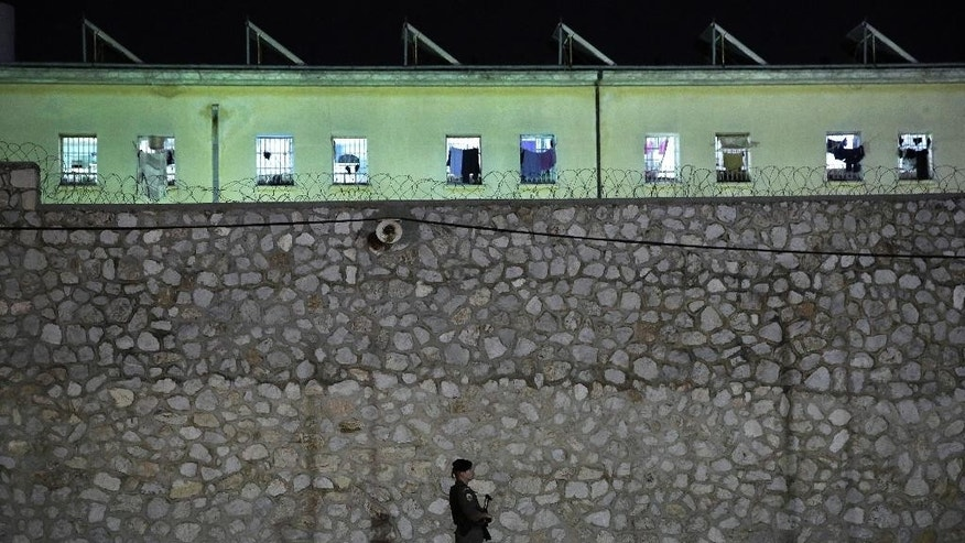 Riot police officers stand guard outside Korydallos Prison on Sunday, May 3, 2015, after two prisoners died, both of Pakistani nationality, and 21 others were injured in a brawl among inmates Sunday, authorities say. All injured people, some in serious condition, have been taken to outside hospitals for treatment.  (AP Photo/Petros Giannakouris)