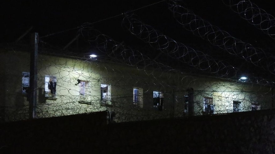 Barbed wire surrounds the Korydallos Prison yard on Sunday, May 3, 2015, after two prisoners died, both of Pakistani nationality, and 21 others were injured in a brawl among inmates Sunday, authorities say. All injured people, some in serious condition, have been taken to outside hospitals for treatment. (AP Photo/Petros Giannakouris)