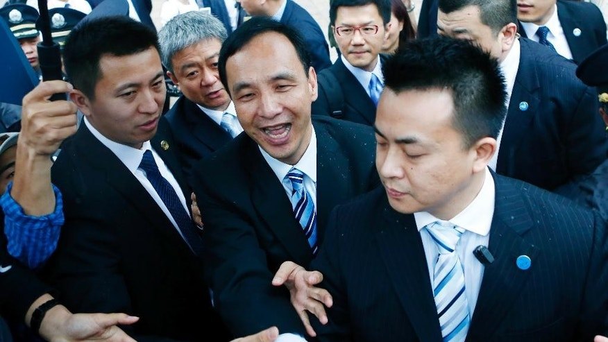 Eric Chu, center, chairman of Taiwan's ruling party Kuomintang shakes hand with crowds as he leaves Fudan University in Shanghai, China, Saturday, May 2, 2015. Chu is leading a delegation to the cross-strait economic, trade and culture forum and will meet with Chinese President Xi Jinping on May 4. (Chinatopix via AP) CHINA OUT