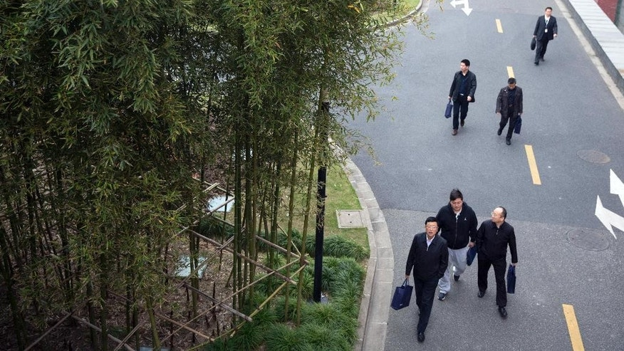 In this photo taken on April 16, 2015, Chinese men arrive at the campus of the China Executive Leadership Academy Pudong (CELAP) in Shanghai, China. Rising Communist Party members from across the country have come to the China Executive Leadership Academy Pudong (CELAP) in Shanghai as part of the party's decade-long effort to introduce its own elite to foreign ideas. Outside these walls, President Xi Jinping's government has been campaigning to scrub Western influence from university lecture halls and discussion groups, but here some 10,000 privileged party loyalists each year hear from top Western scholars, officials and executives, albeit in a controlled environment. (AP Photo/Ng Han Guan)