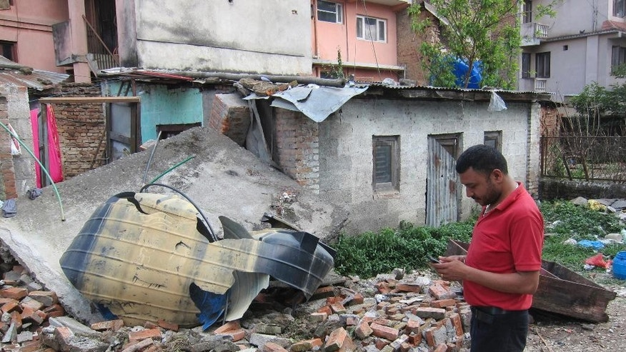 In this May 2, 2015 photo, Nepalese Rajendra Shrestha, 32, stands next to a damaged building near where he now lives in Kathmandu, Nepal. Shrestha and six members of his family now sleep in a one-room shack in the shadow of where they once lived, an 82-year-old brick building that the quake battered into near-collapse. The family feels it is not safe here but stays because they need to protect their cosmetics shop and their possessions. (AP Photo/Foster Klug)