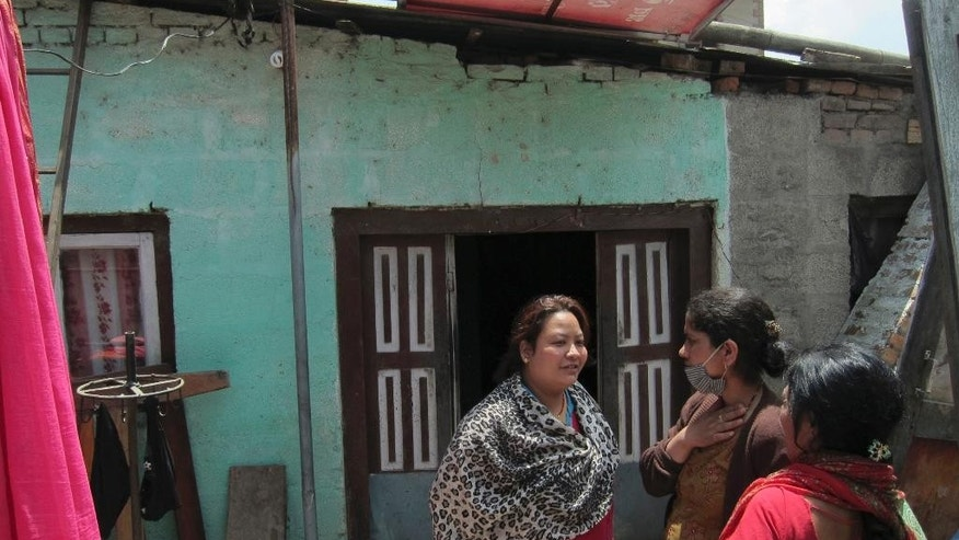 "In this May 2, 2015 photo, Nepalese woman Anu Shreshta, 31, left, talks to neighbors near a one-room shack where she and six members of her family have been living after the April 25 earthquake in Kathmandu, Nepal. ""We're not safe here,"" Shrestha, says. ""I feel I will die now."" The family feels it is not safe here but stays because they need to protect their cosmetics shop and their possessions. (AP Photo/Foster Klug)"