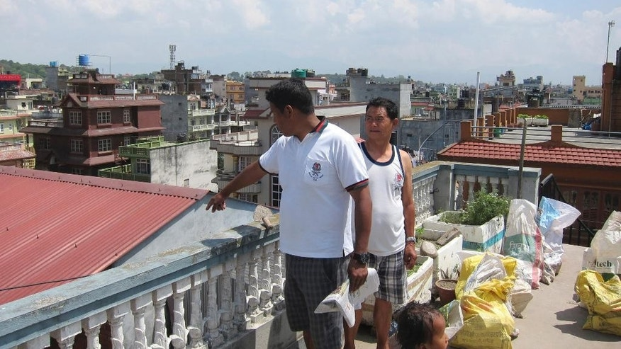 "In this May 2, 2015 photo, Nepalese man Khim Bahadur, 40, left, points to damaged areas from the roof of his four-story home in Kathmandu, Nepal. There are cracks on each floor, and along the foundation. ""I still don't know if it's dangerous or not,"" Bahadur, who works in construction, says. ""I'm maybe 70 percent confident, and 30 percent worried. No one around here knows if their homes are OK. That's the most worrying thing."" (AP Photo/Foster Klug)"
