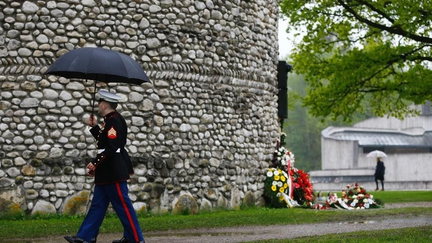 US soldiers walk past wreaths laid on the memorial site for the former Nazi concentration camp in Dachau, southern Germany, Sunday, May 3, 2015 to commemorate the 70th anniversary of the liberation of the camp. (AP Photo/Matthias Schrader)