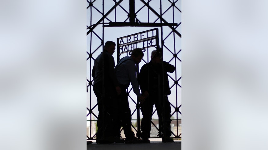 "Blacksmith prepare a replica of the Dachau Nazi concentration camp gate, with the writing ""Arbeit macht frei"" (Work Sets you Free) at the main entrance of the memorial in Dachau, Germany, Wednesday, April 29, 2015. The gate was stolen in November 2014. (AP Photo/Matthias Schrader)"