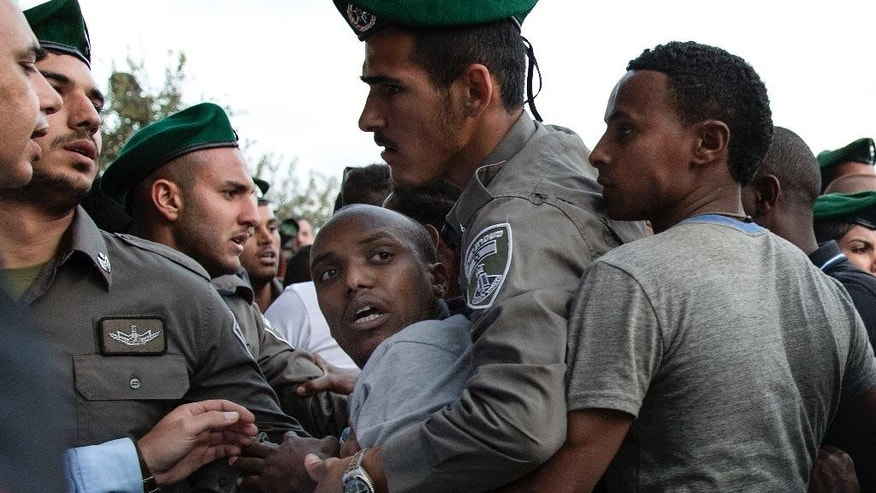 Israeli police detains an Israeli Ethiopian during a demonstration in Tel Aviv, Sunday, May 3, 2015. Several thousand people, mostly from Israel's Jewish Ethiopian minority, protested in Tel Aviv against racism and police brutality on Sunday shutting down a major highway and scuffling with police. (AP Photo/Tsafrir Abayov)