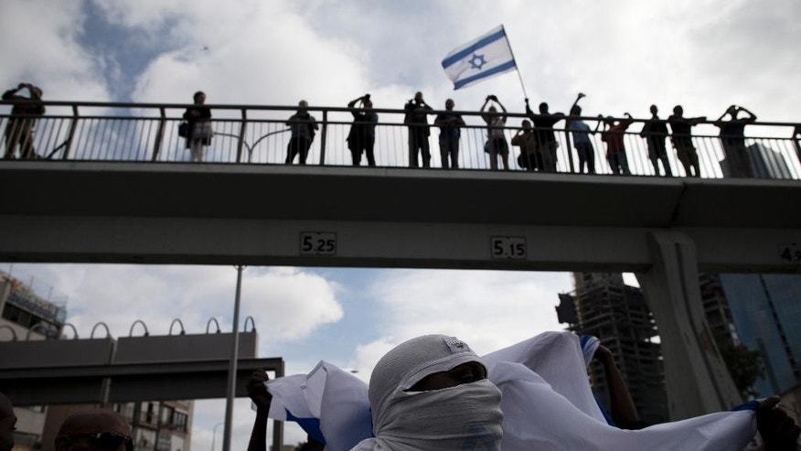 Israel's Jewish Ethiopians block highway during a protest against racism and police brutality in Tel Aviv, Israel, Sunday, May 3, 2015. Several thousand people, mostly from Israel's Jewish Ethiopian minority, protested in Tel Aviv against racism and police brutality on Sunday shutting down a major highway and scuffling with police. (AP Photo/Oded Balilty)