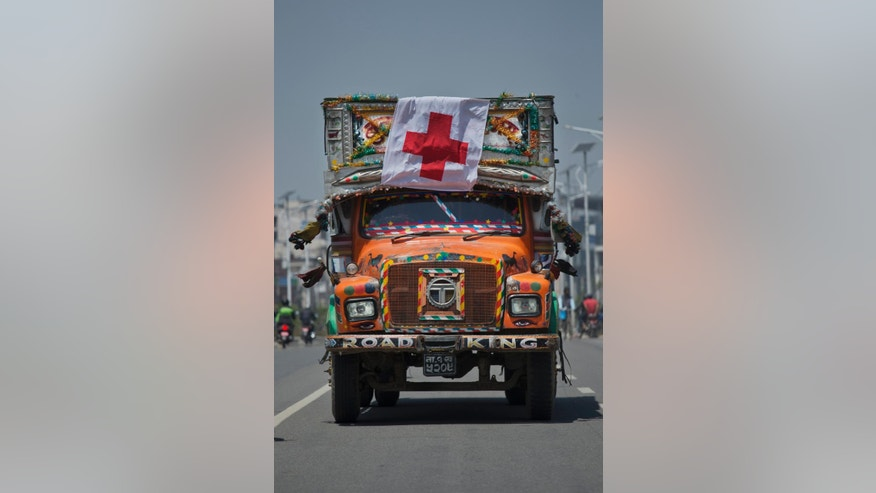 A Nepalese truck with a Red Cross flag drives through the streets of Kathmandu, Nepal, Sunday, May 3, 2015. With monsoon rains expected in a few weeks, Nepal has pleaded with donors to send tents and temporary shelters for earthquake victims who have been living in the open for more than a week, with their homes damaged by the April 25 quake. (AP Photo/Bernat Amangue)