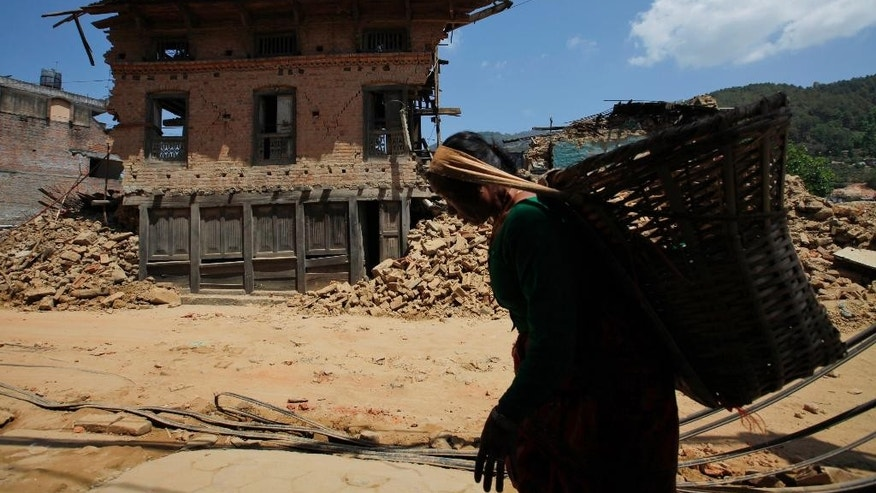 "A Nepali woman carries a basket and walks past a damaged house in the Nepalese capital of Kathmandu on Saturday, May 2, 2015. What is the difference between the words ""Nepali"" and ""Nepalese""? Very little, it seems _ even if the question has come up repeatedly in newsrooms since the April 25 earthquake. (AP Photo/Niranjan Shrestha, File)"