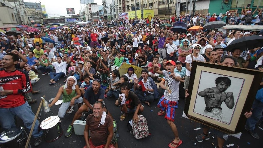 Filipinos watch a live satellite feed of the welterweight title fight between Filipino boxing hero Manny Pacquiao and Floyd Mayweather Jr. during a free public viewing in downtown Manila, Philippines on Sunday, May 3, 2015. Mayweather Jr. won the match. (AP Photo/Aaron Favila)