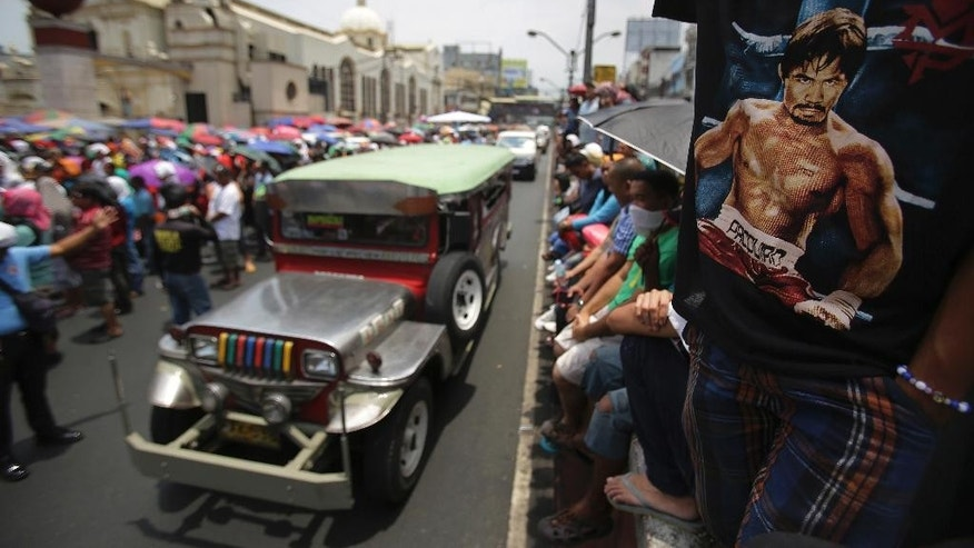 A Filipino wears a shirt bearing Filipino boxing hero Manny Pacquiao as they watch a live satellite feed of the welterweight title fight between Pacquiao and Floyd Mayweather Jr. during a free public viewing in downtown Manila, Philippines on Sunday, May 3, 2015. Mayweather Jr. won the match. (AP Photo/Aaron Favila)