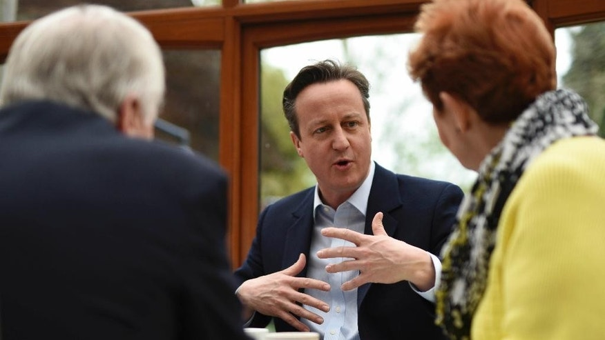 British Prime Minister and leader of the Conservative Party David Cameron, center, speaks with people at a cafe in Cheadle, near Manchester, northwest England, Saturday, May 2, 2015. Britain's most unpredictable general election in decades is Thursday, May 7, with polls showing the two biggest parties — Labour and the Conservatives —running in a virtual dead heat. (Oli Scarff/Pool via AP)
