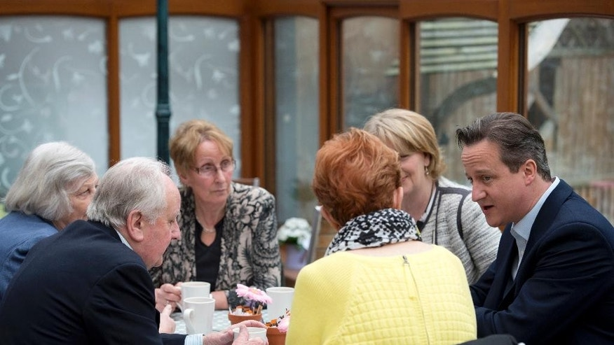 British Prime Minister and leader of the Conservative Party David Cameron, right, speaks with people at a cafe in Cheadle, near Manchester, northwest England, Saturday, May 2, 2015. Britain's most unpredictable general election in decades is Thursday, May 7, with polls showing the two biggest parties — Labour and the Conservatives —running in a virtual dead heat. (Oli Scarff/Pool via AP)