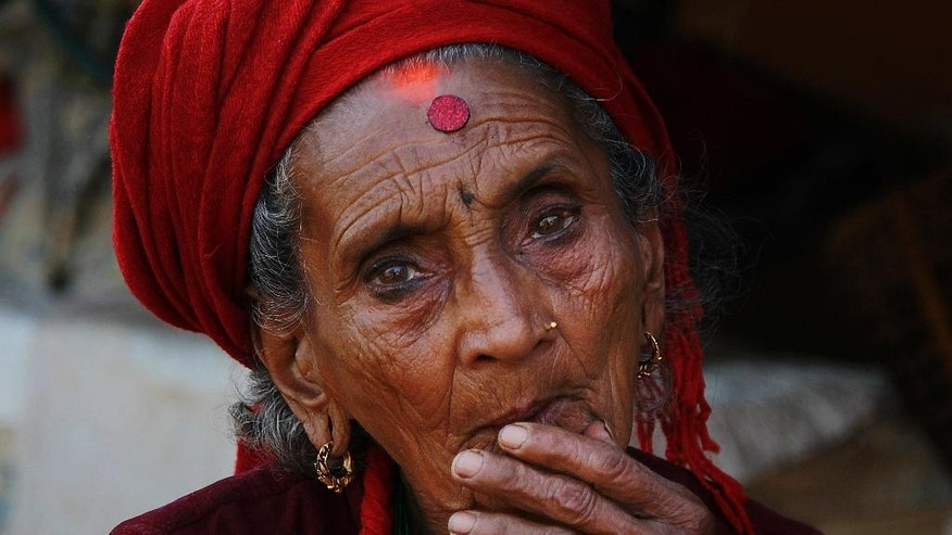 In this photo taken on Saturday, May 2, 2015, Tika Devi Khanal, 81, sits at her damaged home in the destroyed village of Pokharidanda, near the epicenter of the April 25 massive earthquake, in the Gorkha District of Nepal. People in villages reachable by road in Nepal's quake-wracked central Gorkha District are fending for themselves, with the government so short on relief they've been forced to focus only on far-flung reaches of the remote Himalayas. (AP Photo/Wally Santana)