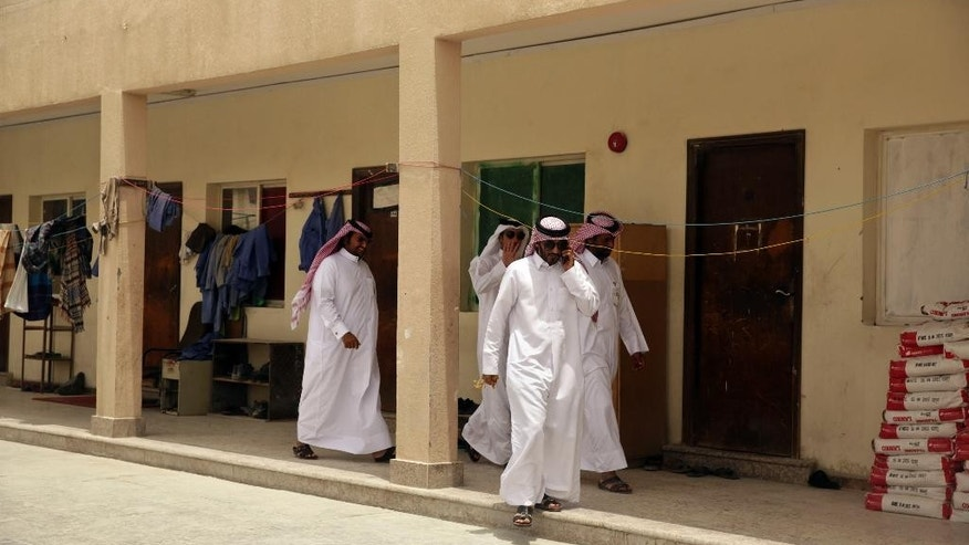 "In this Sunday, May 3, 2015 photo taken during a government organized media tour, Qatari officials visit a housing facility for laborers in Doha, Qatar. This facility has been cited by officials for its poor conditions. Qatar's top labor official told The Associated Press Monday, May 4, 2015, that Qatar's inability to ensure decent housing for its bulging migrant labor population was ""a mistake"" the government is working to fix as it prepares to host the 2022 World Cup, vowing his country would improve conditions for its vast foreign labor force. (AP Photo/Maya Alleruzzo)"