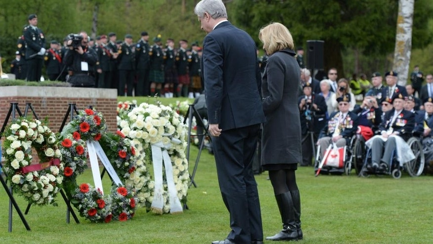 Canadian Prime Minister Stephen Harper and his wife, Laureen Harper, pay their respects to Canada's war dead at the Holten Canadian War Cemetery, near Arnhem, Netherlands, on Monday, May 4, 2015. (Sean Kilpatrick/The Canadian Press via AP)