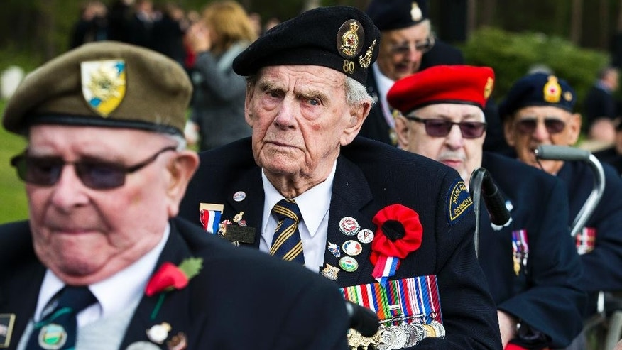 Canadian World War II veteran Frank Graham, center, attends memorial ceremonies in honor of Canadian soldiers who died during the liberation of the Netherlands in 1945 at the Canadian War Cemetery in Holten, east Netherlands, Monday, May 4, 2015. Canadian Prime Minister Stephen Harper is in the Netherlands to mark the 70th anniversary of the Liberation of the Netherlands. (AP Photo/Vincent Jannink)