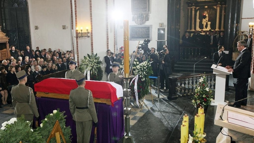 Poland's President Bronislaw Komorowski, standing at right, speaks during a funeral mass at St. John's Arch-Cathedral, in Warsaw, Poland, on Monday, May 4, 2015 for Wladyslaw Bartoszewski, Poland's former foreign minister and a former Auschwitz prisoner who helped save Jews from the Holocaust. Bartoszewski, a historian, writer and politician, died suddenly on April 24 at the age of 93. (AP Photo/Czarek Sokolowski)