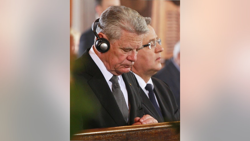 German President Joachim Gauck, left, and Poland's President Bronislaw Komorowski pray during a funeral mass at St. John's Arch-Cathedral, in Warsaw, Poland, Monday, May 4, 2015 for Wladyslaw Bartoszewski, Poland's former foreign minister and a former Auschwitz prisoner who helped save Jews from the Holocaust. Bartoszewski, a historian, writer and politician, died suddenly on April 24 at the age of 93. (AP Photo/Czarek Sokolowski)